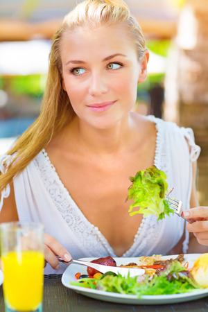 Portrait of attractive woman eating fresh green salad using knife and fork, having lunch in outdoors restaurant, healthy lifestyle concept photo