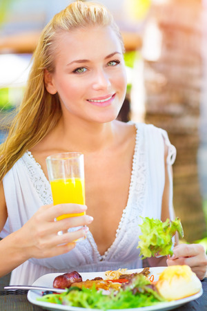Closeup portrait of beautiful young happy female having lunch outdoors, drink refreshing orange juice and eating green salad, healthy eating concept photo