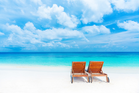 sunbed: Two empty sunbed on the beach, beautiful seascape, relaxation on Maldives island, luxury summer vacation concept Stock Photo