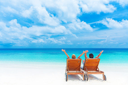 Two happy people relaxing on the beach, sitting on comfortable sunbed with raised up hands for joy, rear view, summer holidays concept     Stock Photo