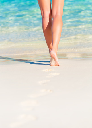 Closeup photo of sexy woman legs, body part, slim female walking on the beach, carefree lifestyle, summer vacation, relaxation concept photo