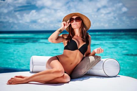 유행 모자와 선글라스, 고급 여름 휴가 개념을 입고 해변에 아늑한 흰색 안락에 앉아 섹시 한 여자, 세련된 모델 스톡 콘텐츠