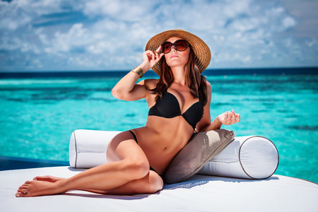 Reizvolle Frau auf weiß gemütliche Liege am Strand sitzen, stilvolle Mode Modell trägt Hut und Sonnenbrille, Luxus-Ferien-Konzept