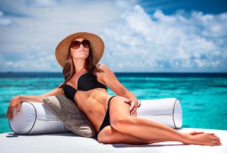 Sexy vrouw op het strand, aantrekkelijk model draagt hoed en zonnebril zittend op de bank op luxe Maldives Resort, zomervakantie concept Stockfoto