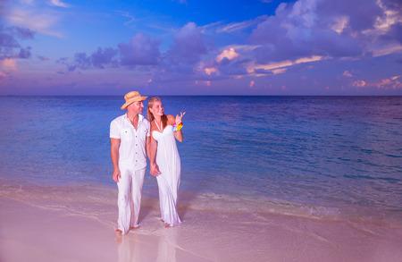 Wedding on the beach, happy couple walking along beautiful sandy island, young family holding hands and enjoying sunset, honeymoon vacation on Maldives photo