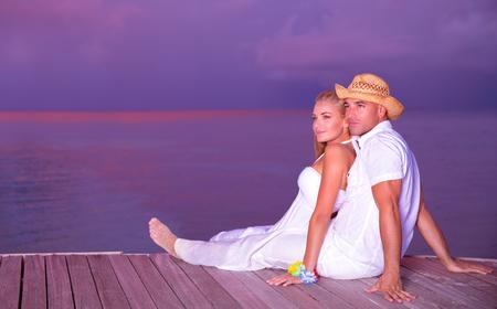 Wedding on the beach, happy couple sitting on wooden deck, luxury resort on an island, young family enjoying sunset, honeymoon vacation on Maldives Stock Photo - 28757753