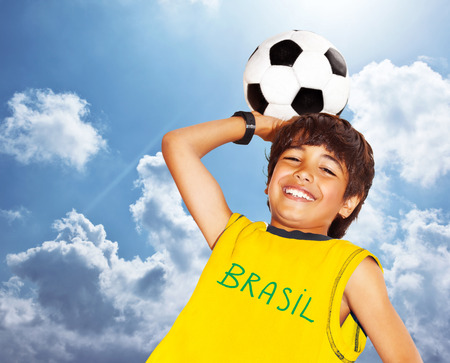 boy ball: Cute boy playing football outdoor, happy child, young male teen goalkeeper enjoying sport game, holding ball, portrait of a preteen smiling and having fun, kids activities, little footballer over blue sky background