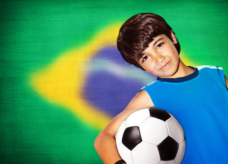 Cute boy playing football, happy child, young male teen goalkeeper enjoying sport game, holding ball, portrait of a healthy preteen having fun, kids activities, little footballer photo