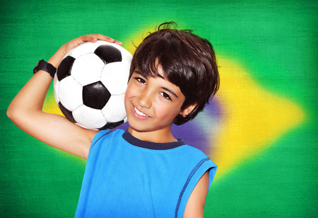 Cute boy playing football, happy child, young male teen goalkeeper enjoying sport game, holding ball, portrait of a preteen smiling and having fun, kids activities, little footballer photo