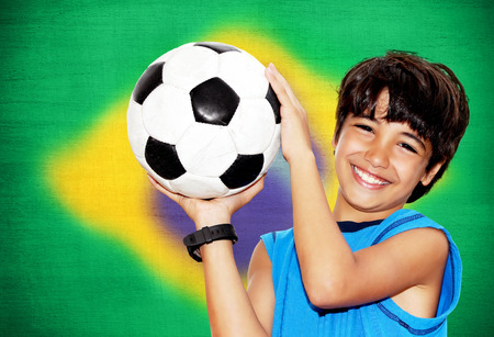 boy ball: Cute boy playing football, happy child, young male teen goalkeeper enjoying sport game, holding ball, portrait of a preteen smiling and having fun, kids activities, little footballer