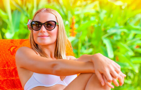 Portrait of beautiful woman sitting on sunbed in the tropics, enjoying exotic nature, sunny day, relaxation outdoor, luxury summer holidays concept