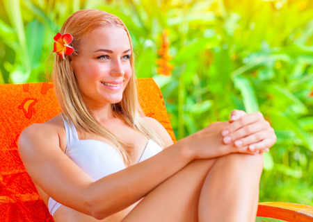 Cute female on tropical resort, woman sitting on deckchair and smiling, pretty girl enjoying exotic nature, summer vacation concept