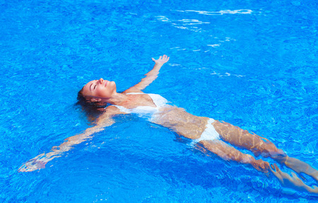 Female enjoying summer holidays, woman on day spa relaxation, sexy girl in the pool, leisure and recreation concept photo