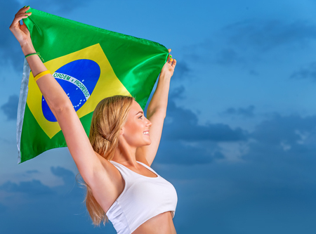 Happy fan of Brazilian football team, cheerful pretty girl on stadium cheering in support, holding up big national flag of Brazil, active people traveling to World Cup  photo