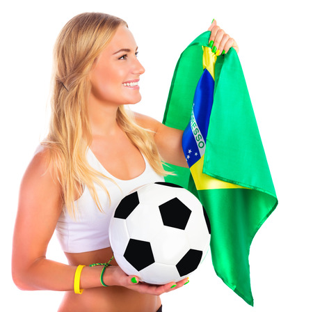 Portrait of happy football fan isolated on white background, attractive female holding in hand ball and Brazilian flag, football competition concept photo