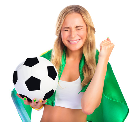 Portrait of happy excited Brazilian football team fan with closed eyes isolated on white background, holding in hand ball and Brazil flag, winning in championship concept photo