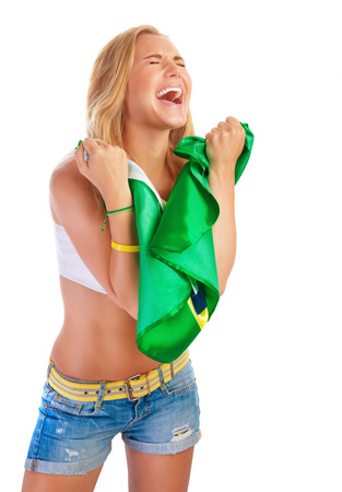 Portrait of beautiful young girl is glad to the goal that Brazil hammered, holding in hands Brazilian flag and screaming of pleasure with closed eyes, isolated on white background photo