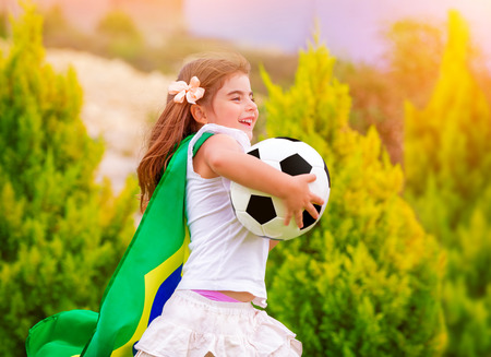 Little active football fan running on the green grass field with ball, young supporter of Brazilian football team with national flag  photo