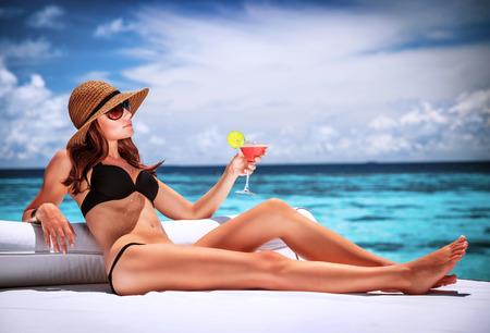 vacanza al mare: Donna sexy rilassante sulla spiaggia resort di lusso, seduta sul lettino e bere cocktail, concetto di vacanza estiva