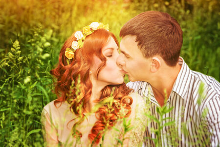 Closeup portrait of gentle young couple kissing outdoors, spending wedding day in the park, romantic date, love concept photo