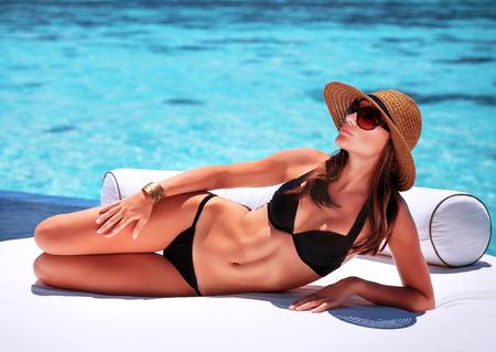 Mujer sexy bronceado en la playa, acostado en el sofá blanco de lujo, pasar las vacaciones de verano en centro turístico de las Maldivas