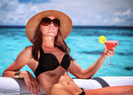 Portrait of sexy gorgeous female relaxing on luxury beach resort, sitting on lounger and drinking cocktail, summer vacation concept