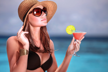 Portrait of stunning woman wearing stylish beach hat and sunglasses drinking cocktail outdoors, summer vacation on Maldives resort photo