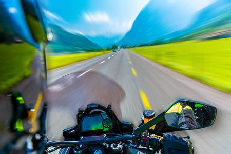 山岳地帯の高速道路に乗って極端なスポーツ、アルプス、夏の冒険スピード コンセプトに沿ってツーリング バイクのスローモーション