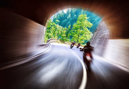 slow motion: Group of bikers touring along European mountains, riding in tunnel, extreme lifestyle, slow motion, traveling and tourism concept