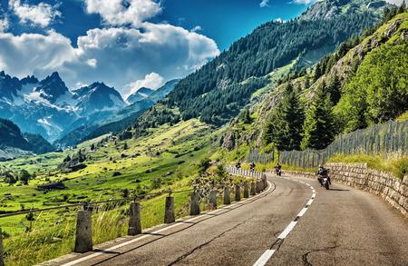 Grupo de motociclistas que recorren en la carretera montañosa
