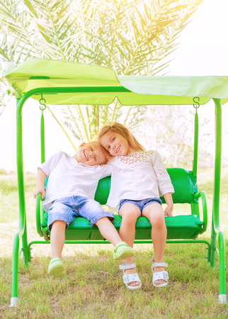 Portrait of two happy kids on swing, enjoying entertainment in summer camp, carefree childhood, active lifestyle, friendly family concept photo
