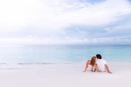 Romantisch paar zittend op het strand en genieten van mooi uitzicht op zee, zijaanzicht, tijd samen, de zomer vakantie concept Stockfoto