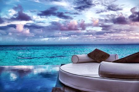 럭셔리 비치 리조트, 수영장 주변의 아름다운 아늑한 흰색 안락, 신혼 여행을위한 완벽한 장소, 흐린 날씨에 화려한 바다, 여름 휴가 개념