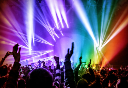 Happy young people having fun on rock concert in nightclub, colorful glowing lights, enjoying popular music, partying concept photo
