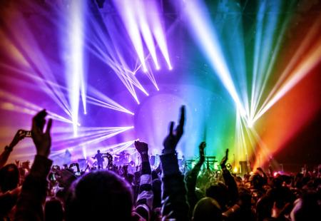 foule mains: Jeunes heureux qui s'amusent sur un concert de rock dans la discoth�que, les lumi�res rougeoyantes color�es, profiter de la musique populaire, la f�te notion Banque d'images