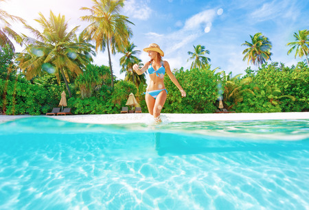 Woman comes into water on the beach, beautiful tropical island, luxury summertime vacation, happiness and freedom concept Stock Photo - 29870428