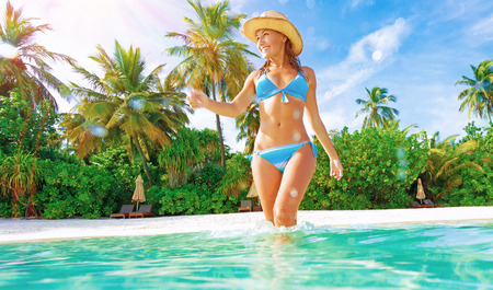 Cute slim female wearing stylish blue swimsuit comes into sea, enjoying summer vacation on Maldives island, joy and fun concept Stock Photo - 29870430