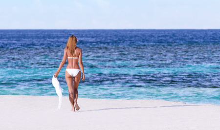 Sexy woman walking on the beach, back side, perfect body, luxury summer holidays on Maldives, travel and vacation concept  photo