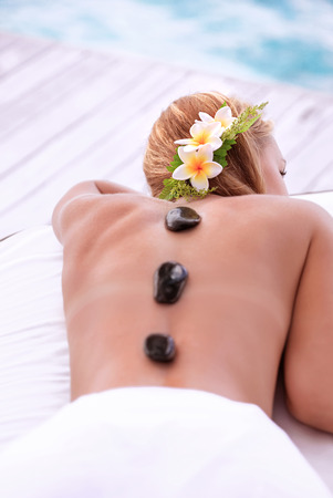 Enjoying day spa, cute female with frangipani flowers in hair lying down on massage table on the beach, black hot stones therapy, zen balance concept photo
