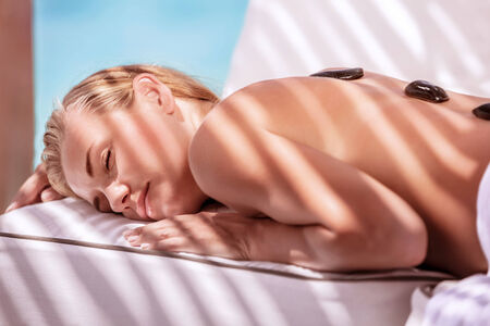 Gorgeous female spending summer vacation on luxury spa resort, massage procedure with black hot stones on the beach Stock Photo - 29870474