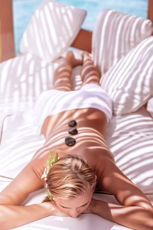 Sexy woman on luxury spa massage with hot stones, alternative therapy, wellness procedure outdoors, summer vacation concept Stock Photo - 29870487
