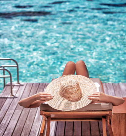 Young woman sitting on wooden pier on the sea wearing hat and taking sun bath, enjoying perfect summer day, traveling and luxury vacation concept