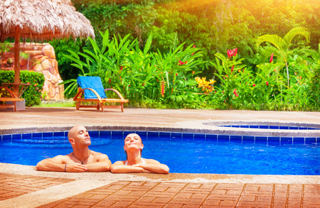 Happy couple enjoying pool, young family on day spa relaxation, luxury vacation on tropical resort, romantic travel destination  photo