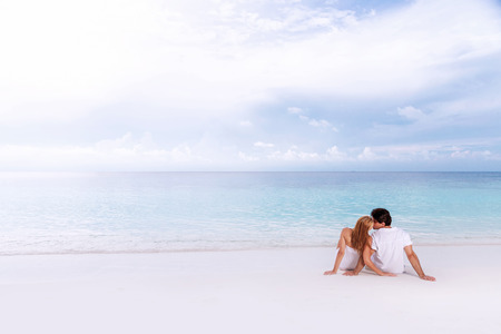 Rear view of loving couple relaxing on the beach, kissing outdoors, boyfriend with girlfriend enjoying summer holidays on luxury Maldives resort, love and romance concept  Фото со стока