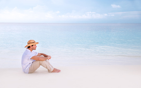 near side: Thoughtful man sitting on the beach, side view, looking away, relaxation near sea, enjoying seascape, summer holidays and vacation concept