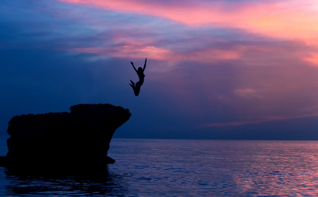 purple sunset: Brave girl jumping from the rocks in the evening on beautiful purple sunset background, summer adventure, freedom concept