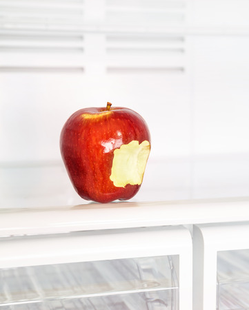 Closeup photo of big red bitten apple in the empty fridge, fruits diet, healthy lifestyle, organic nutrition, weight lost concept photo
