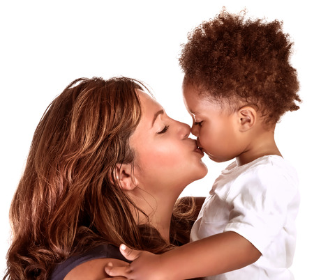 Portrait of cheerful mother kissing baby, studio shot, happy motherhood, lovely African family, happiness and love concept photo