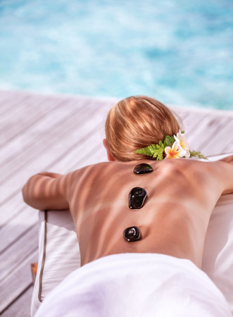 Hot stone massage on luxury spa resort on the beach, young beautiful woman lying down outdoors and enjoying dayspa, summer vacation concept photo