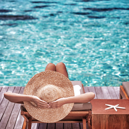 sit on: Young woman sitting on wooden pier on the sea wearing hat and taking sun bath, enjoying perfect summer day, traveling and luxury vacation concept